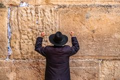 Believing pray near the wall of crying in a black hat. Believing pray near the wall of crying in a big black hat raising his hands uphill royalty free stock image