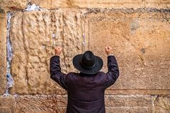 Believing pray near the wall of crying in a black hat. Believing pray near the wall of crying in a big black hat raising his hands uphill stock photos
