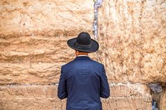 Believing pray near the wall of crying in a black hat. Believing pray near the wall of crying in a big black hat stock images