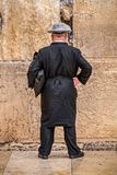 Believing pray near the wall of crying in a black hat. Believing is praying near the wall of crying in a big black hat in a raincover under the rain stock photography