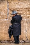 Believing pray near the wall of crying in a black hat. Believing is praying near the wall of crying in a big black hat in a raincover under the rain royalty free stock photo