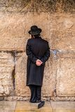 Believing pray near the wall of crying in a black hat. Believing is praying near the wall of crying in a big black hat in a raincover under the rain royalty free stock photography