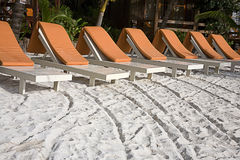 Belize beach scene. Seven beach lounge chairs were dragged into place.  The impression of the chair legs makes an interesting pattern.  The orange comfort pads Royalty Free Stock Photos