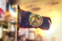 Belize Flag Against City Blurred Background At Sunrise Backlight. Sky Royalty Free Stock Photo