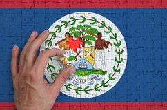 Belize flag is depicted on a puzzle, which the man`s hand completes to fold.  vector illustration