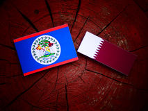 Belize flag with Qatari flag on a tree stump isolated. Belize flag with Qatari flag on a tree stump Royalty Free Stock Image