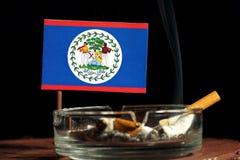 Belize-Flagge mit brennender Zigarette im Aschenbecher lokalisiert auf Schwarzem Stockfoto