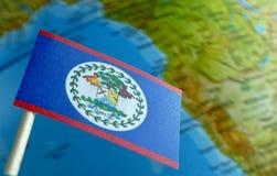 Belize-Flagge mit einer Kugelkarte als Hintergrund Stockbilder