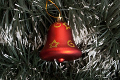 Bell. Red christmas bell  on spruce background Royalty Free Stock Images