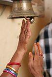 Bell. Two hands reaching for a bell at a fort in Bikaner, India Stock Image