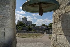 The bell in the ancient Chersonese and the Cathedral of St. Vlad. Ancient bell and the Cathedral of St. Vladimir in the background royalty free stock photo