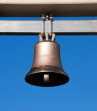 Bell. A bronze bell on blue sky hanging on a beam royalty free stock photo