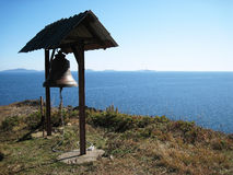 Bell on a cliff in the sea Stock Image