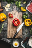 Bell colorful paprika peppers cooking preparation. Paprika on wooden cutting board with kitchen knife, minced meat, egg and season Stock Photo