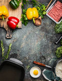 Bell colorful paprika peppers stuffing preparation with cooking ingredients: ground meat, egg, fresh green seasoning and iron po Royalty Free Stock Image