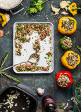 Bell colorful paprika peppers stuffing preparation with rice and mincemeat on rustic kitchen table background Royalty Free Stock Photo
