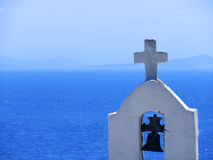 Bell and Cross. Small bell tower with cross on the background of clear sea Stock Images