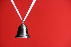 Bell d'argento su colore rosso Fotografia Stock Libera da Diritti