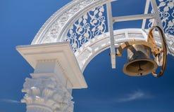 Bell, die im Bogen über Hintergrund des blauen Himmels hängt Lizenzfreie Stockfotografie