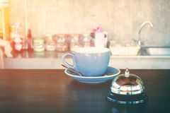 Bell e tazza di caffè calda sul contatore della caffetteria per l'allarme o wark sul concetto Fotografia Stock Libera da Diritti