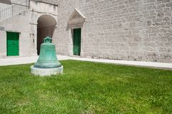 Bell, grass, doors and church. Green church bell in the grass and white, stone built church facade with two green doors Stock Photos
