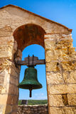 Bell hanging in arch over blue sky background Stock Photos