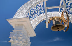Bell hanging in arch over blue sky background Royalty Free Stock Photography