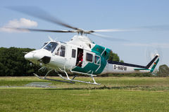 Bell 412 helicopter. AHLEN, GERMANY - JUN 5, 2016: Close up view of a Bell 412SP helicopter kicking up grass while landing Royalty Free Stock Image