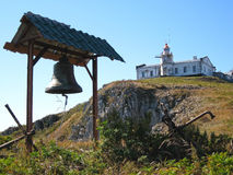 Bell and the lighthouse on the cliff Royalty Free Stock Images
