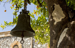 Bell on an orange tree. Old bell under an orange tree stock image