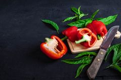 Bell pepper cut in half on a wooden cutting board on a black bac royalty free stock images