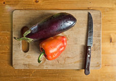 Bell pepper, eggplant and knife on cutting board. Filtered. Red bell pepper, eggplant and knife on wooden cutting board. Top view on kitchen table. Still life Stock Photography