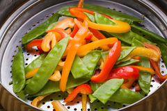 Bell pepper and snow peas stir-fry in stainless steel colander. royalty free stock photos