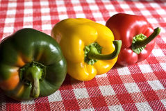 Bell pepper trio. Bell peppers in three colors: green, yellow, red, on a picnic cloth royalty free stock image