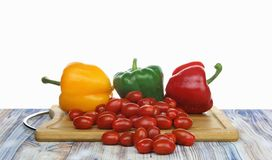 Bell peppers and baby tomatoes on a chopping board white background royalty free stock photos