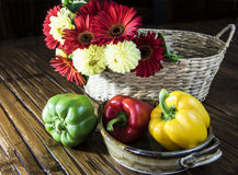 Bell Peppers with Basket of Flowers Stock Photo