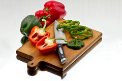 Bell peppers being cutted at wooden cutting board Royalty Free Stock Photo
