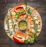 Bell peppers, canned peas, sliced carrots, potatoes and herbs on a cutting board wooden rustic background top view vegetarian c Royalty Free Stock Photo