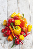 Bell peppers, chili and habaneros on white wood royalty free stock image