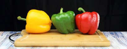 Bell peppers on a chopping board black background stock images