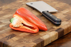 Bell peppers and cleaver on cuttingboard Royalty Free Stock Image