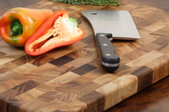 Bell peppers and cleaver on cuttingboard Stock Images