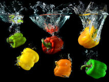Bell peppers droping in to clean water Stock Photos
