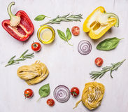 Bell peppers, oil, rosemary, cherry tomatoes and other ingredients for cooking vegetarian pasta, lined frame wooden rustic back Royalty Free Stock Photos