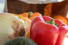 Fresh peppers and onions with brown paper bag. Bell peppers, onion, brown paper bag close up, fresh healthy vegetables Stock Photos