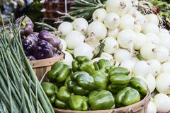 Bell peppers and onions. Fresh organic and locally grown bell peppers, white onnion and green onion on sale at local farmers market Royalty Free Stock Photo