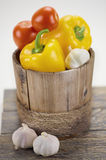 Bell peppers,  tomatoes and some garlic. In a wooden bucket on a wooden plate Royalty Free Stock Images