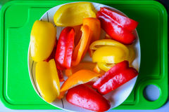 Bell peppers in white plate. Slices of bell peppers in a white plate on the green plastic board Stock Photo