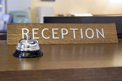 Bell with reception sign on front desk. In hotel. Made with shallow depth of field, focus on reception sign Stock Image
