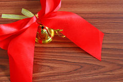 Bell with ribbon over wooden background Stock Images